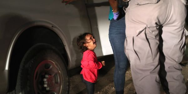 A Getty photographer tells the story behind a heartbreaking photo he took of a migrant girl sobbing while agents questioned her mom at the border